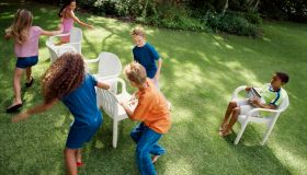 Children playing 'musical chairs' in back yard