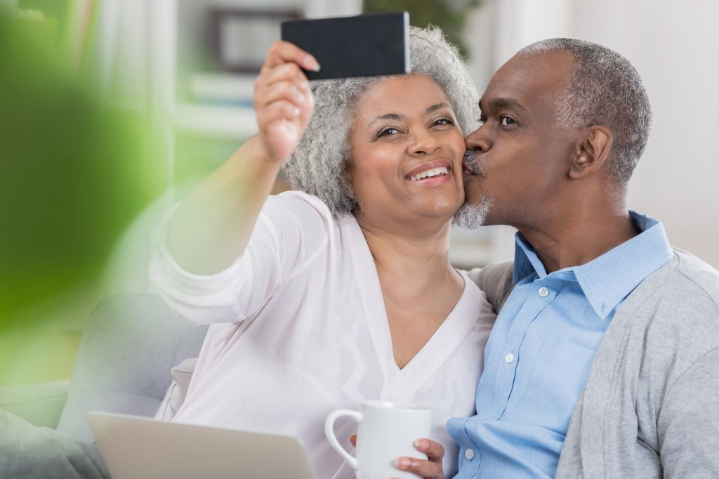 Senior couple pose for selfie at home