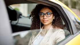 Businesswoman listening to music while commuting to work by taxi
