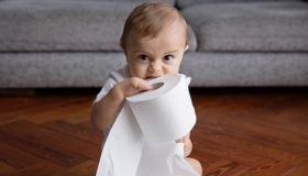Baby boy with blond hair sitting on hardwood floor, playing with toilet paper rolls.