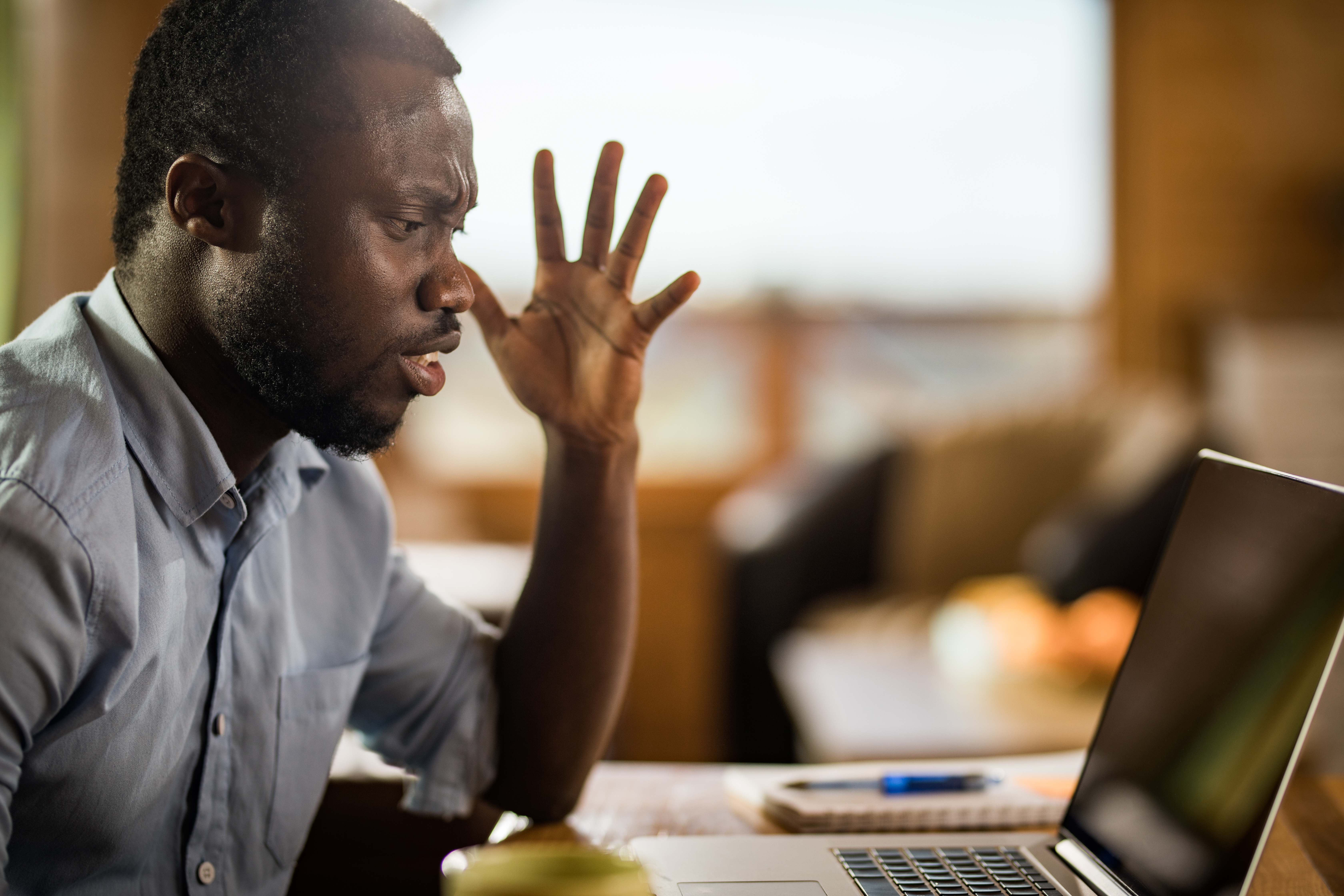 Frustrated black man reading annoying e-mail on laptop at home.