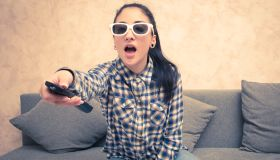 Young Woman Holding Remote Control While Sitting On Sofa At Home