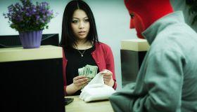 Criminal Robber Robbing an Asian Retail Bank Teller at Counter