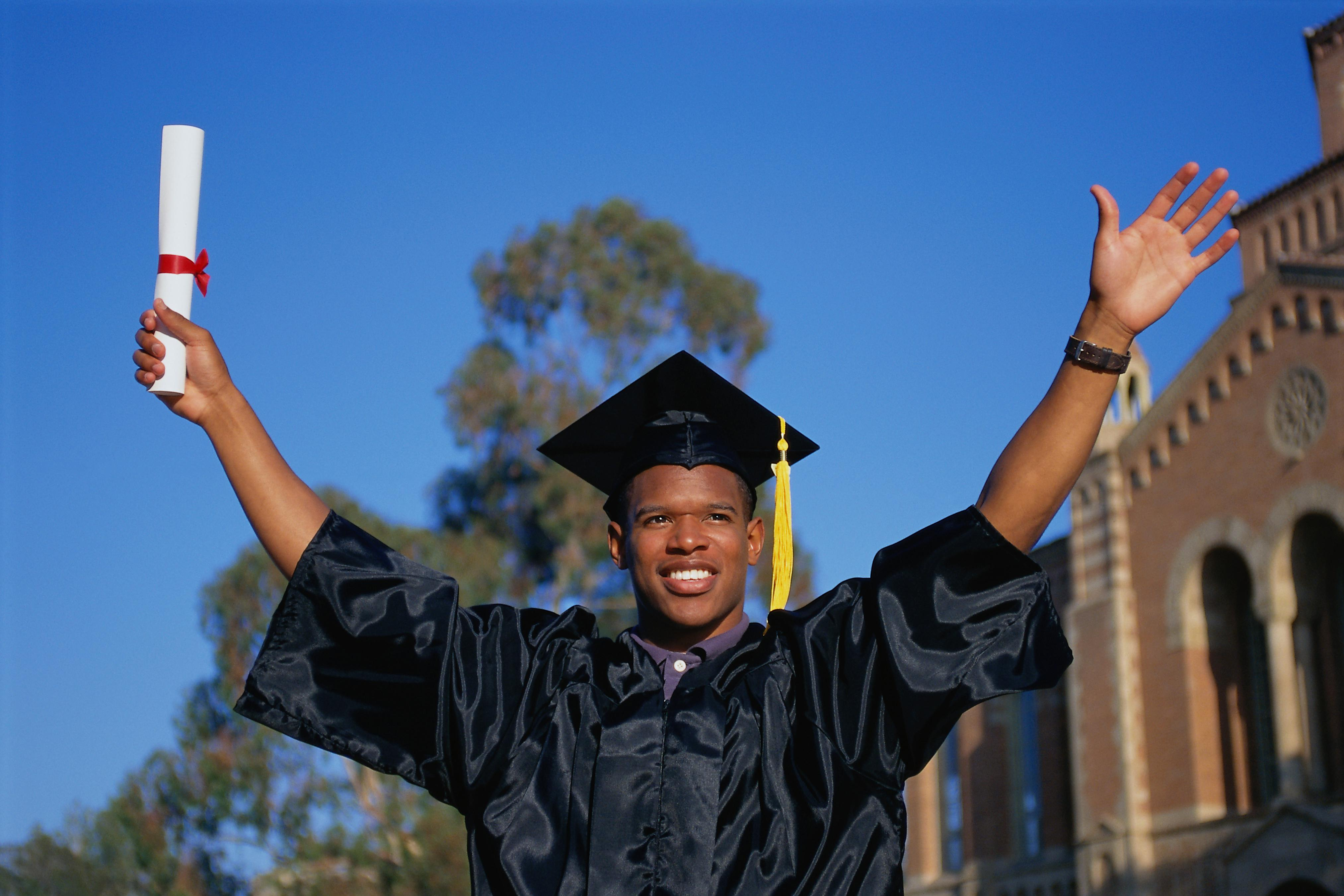 PERBE081 Young man celebrating college graduation,