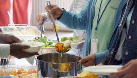 Unrecognizable volunteer serves soup in soup kitchen