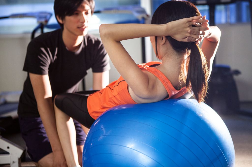 Man and woman working out with exercise ball in gym.
