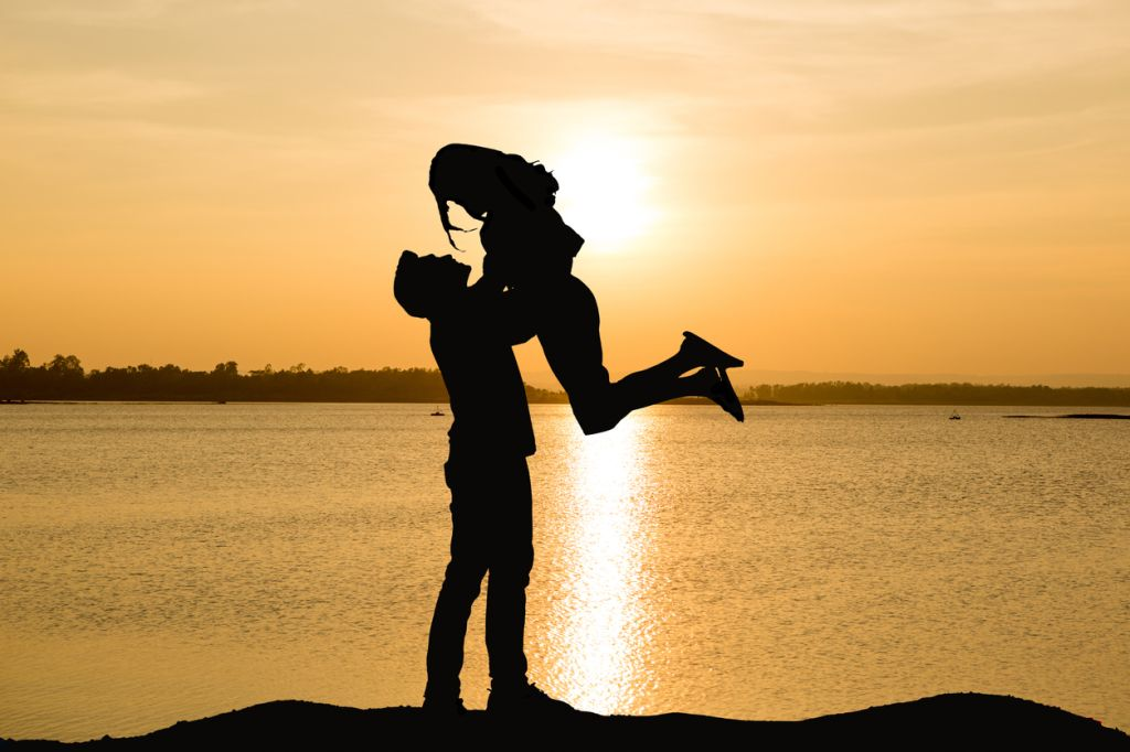 Silhouette Man Lifting Woman By Lake During Sunset