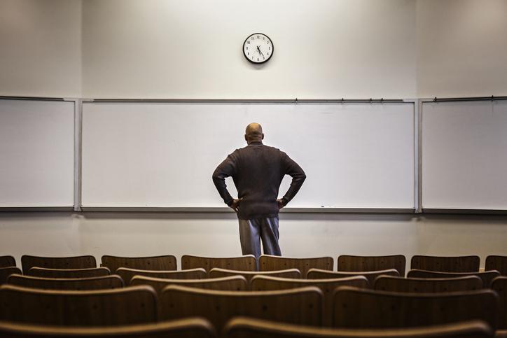 Professor standing in empty classroom