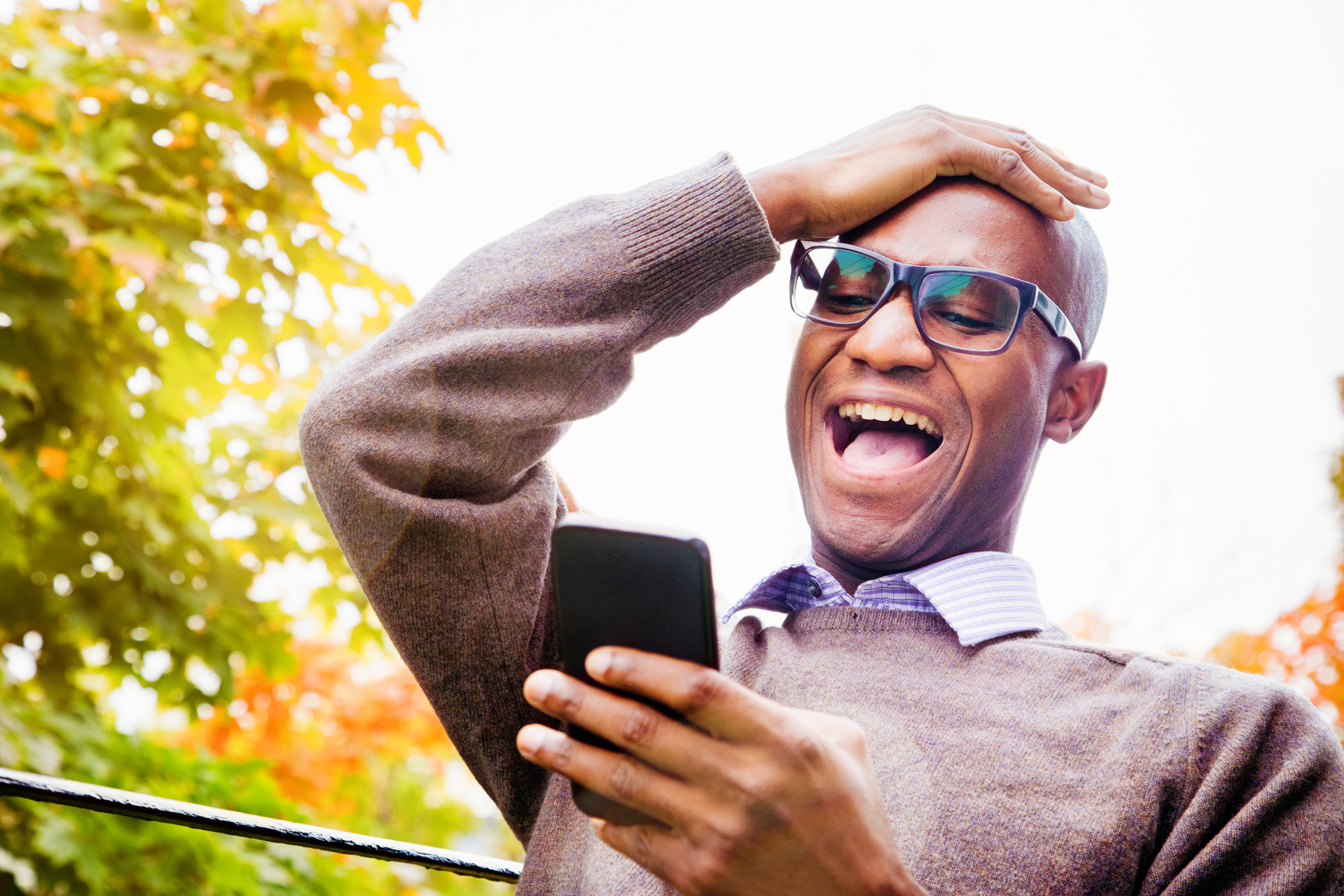 Mature man laughs out loud at story on mobile phone