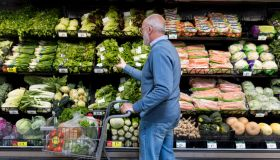 Man shops for leafy greens in grocery store