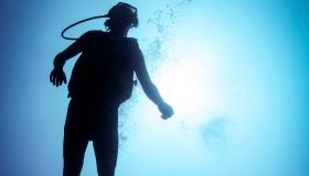 Silhouetted male scuba diver in ocean, Bali, Indonesia