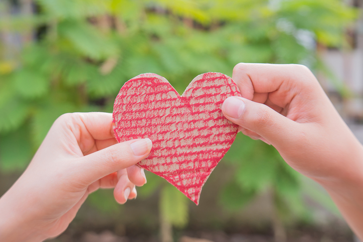 Close-Up Of Hand Holding Heart Shape Against Blurred Background