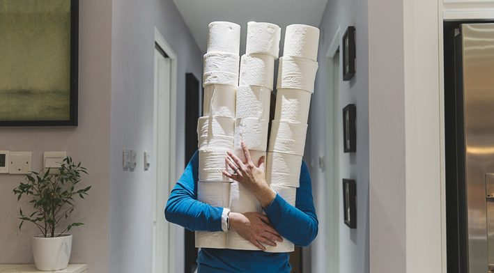 Person holding large piles of toilet rolls