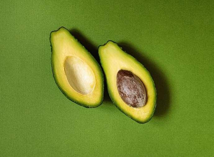 halved avocado on green background, healthy food, superfood, ketogenic diet, vegetarian, healthy fats, healthy lifestyle, wellbeing