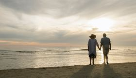 Back view of senior couple standing hand in hand on the beach watching sunset, Liepaja, Latvia