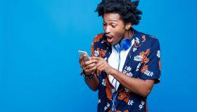 Shocked young man in hawaiian shirt holding smart phone
