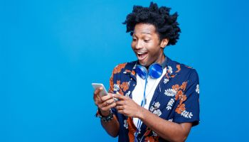 Surprised young man in hawaiian shirt holding smart phone