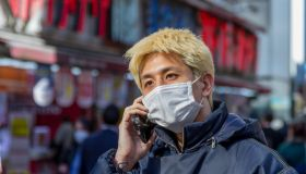 A man with hair dyed blonde wears a face mask as a...