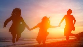 Silhouette Friends Holding Hands While Jumping At Beach Against Orange Sky