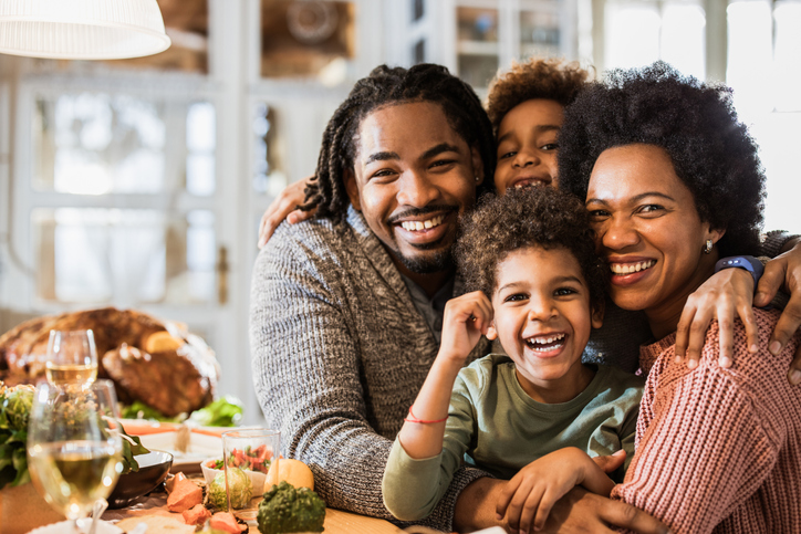 Embraced African American family during Thanksgiving meal at dining table.
