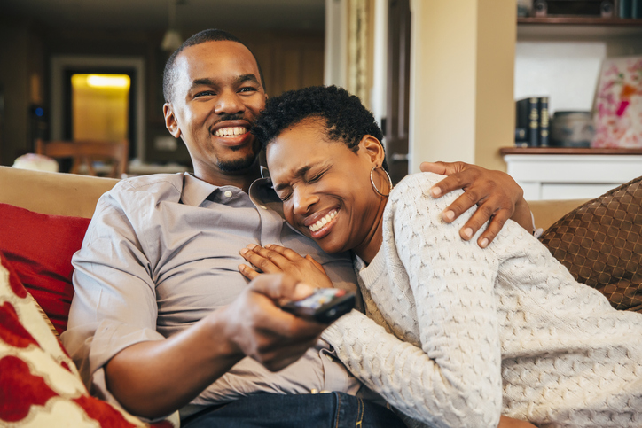 Black couple watching television on sofa