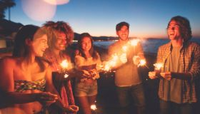 Group of friends playing with sparklers and fireworks on the beach at sunset.