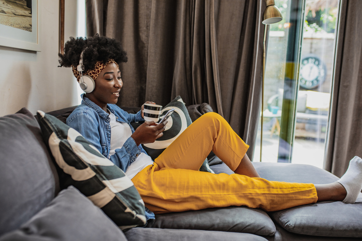 A young African-American woman is relaxing at home and using mobile phone