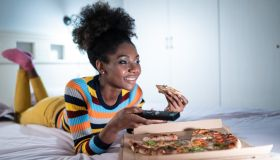 Afro woman spending lonely evening in bed with pizza and watching tv