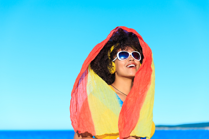 African woman in yellow outfit listen music on the beach