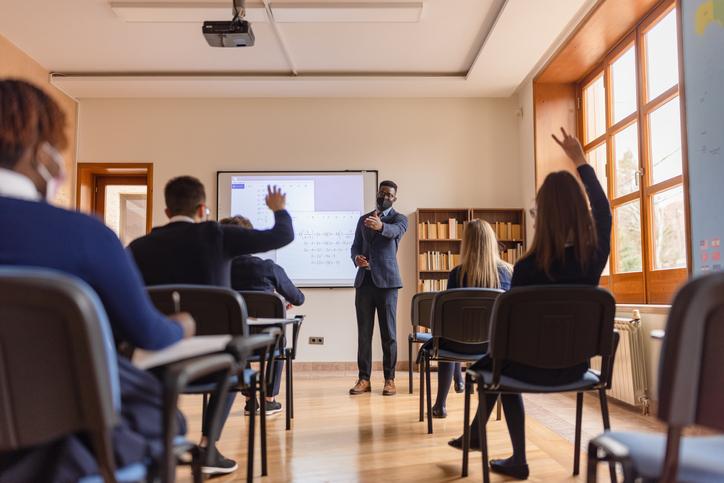 High school teacher giving a lecture, using smart board
